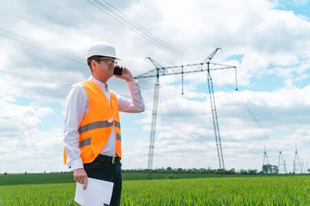 Engineer working near transmission lines. Electrical engineer checks high voltage lines. Transmission towers