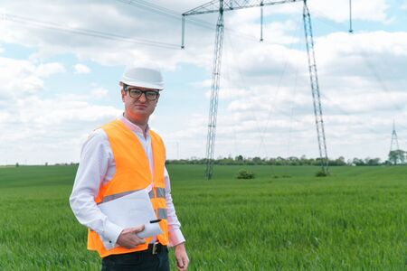 Engineer working near transmission lines. Transmission towers