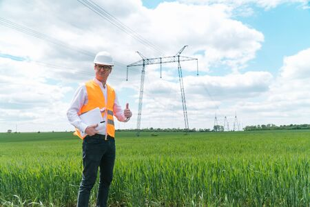 Engineer working near transmission lines. Electrical engineer checks high voltage lines. Transmission towers. Energy efficiency conception