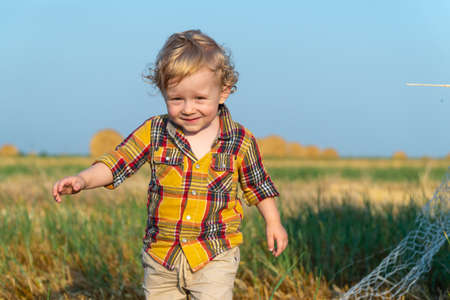 Little fair-haired boy playing on a wheat field with bales