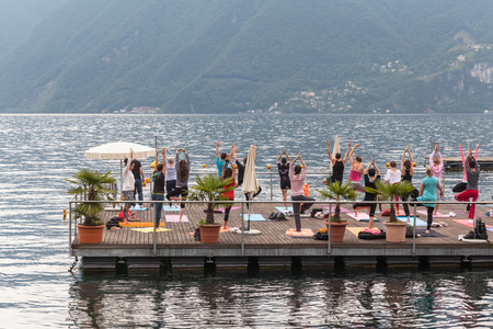 Lugano - June 23, 2013 - People doing Yoga exercise on Lugano lake in the morning on June 23, 2013