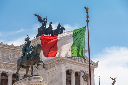altar of fatherland: View of Italian national flag in front of Altare della Patria (Altar of the Fatherland) , the equestrian sculpture of Victor Emmanuel and statue of the goddess Victoria riding on quadrigas on top.