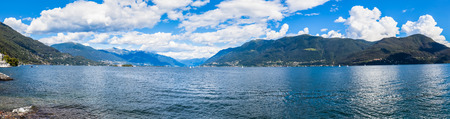 cloud scape: Panorama view of Lake Maggiore with beautiful cloud scape, blue sky and mountains in summer. Photo taken in Brissago, a small town near Locarno, Ticino, Switzerland