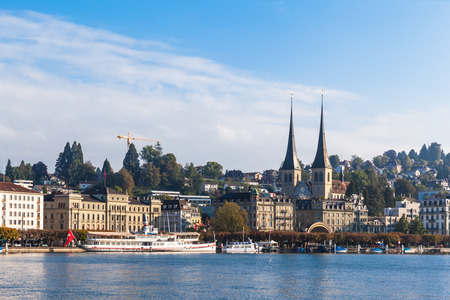 urban architecture: View of Lucerne on the lake side, the famous St. Leodegar church, on a sunny summer day with clouds and blue sky, in Switzerland