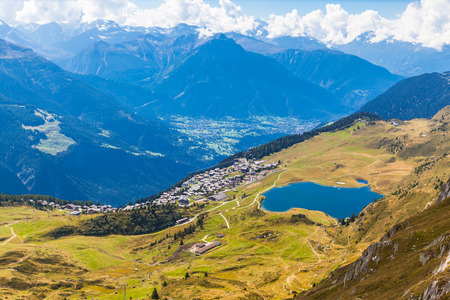 aletsch: Aerial view of the Bettmersee (Lake) and the Bettmer town, with the numerous peaks of alps as background, in Valais, Switzerland, near the famous Aletsch glacier Stock Photo