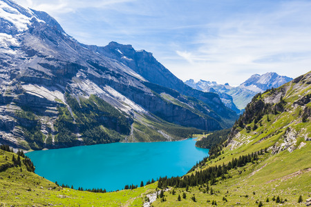 the bernese oberland: The panorama in summer view over the Oeschinensee (Oeschinen lake) and the alps on the other side near Kandersteg on bernese oberland in Switzerland.
