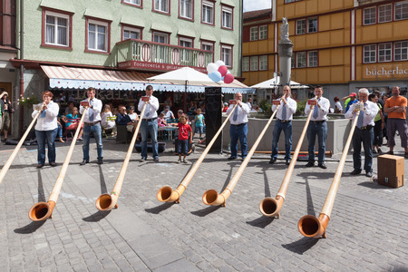 alphorn: Appenzell, Switzerland - August 11, 2013 - Group of musicians playing the Alphorn (traditional instrument consisting of a wooden natural horn of conical bore in alps) on the Landlerfest of Kanton Appenzell in Switzerland.