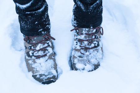foot steps: Feet with hiking boots in snow concept of winter hiking