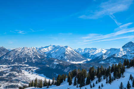 Panorama view of snow covered Austrian Alps in winter above the small town Reutte, with ski slope and skiing people in foreground, Tyrol, Austria