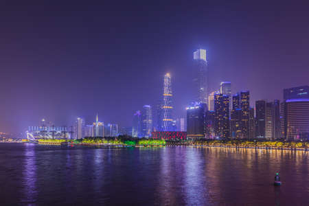 Stunning view of the central business area of Guangzhou on the riverside of  Zhujiang River with illuminated skyscrapers and reflection in water, Guangdong Province, China