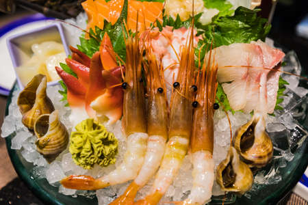 Closeup view of typical Japanese food Sashimi,  a Japanese delicacy consisting of very fresh raw meat, fish, seafood sliced into thin pieces.