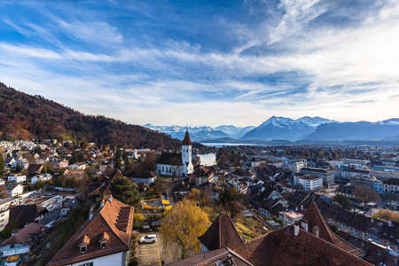 Stunning aerial panorama view of Thun cityscape and Aare river flowing to Lake Thun from Thun castle, with Swiss Alps mountain peaks on Bernese Oberland in background, a sunny autumn day, Switzerland