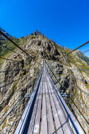 Stunning view on the Trift bridge, a suspension bridge over the Triftsee, glacier, in Gimsel on Bernese Oberland, Switherland.