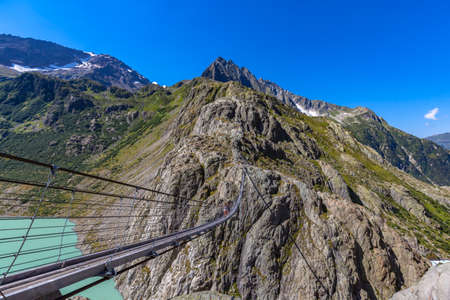 Breath taking view of the Trift bridge, a suspension bridge over the Triftsee, glacier, in Gimsel on Bernese Oberland, Switherland.