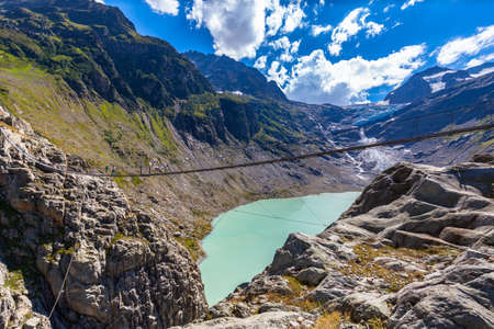 Stunning view of the suspension bridge, Trift bridge over the Trift lake (Triftsee) and glacier, Canton of Berne, Switzerland. Imagens