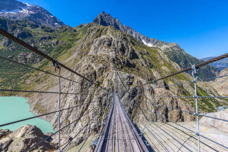 Breath taking view on the Trift bridge, a suspension bridge over the Triftsee, glacier, in Gimsel on Bernese Oberland, Switherland.