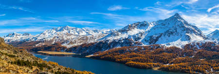 Panoama view view of Sils lake and the swiss alps in Upper Engadine with golden trees in autumn, Canton of Grisons, Switzerland. Stock fotó