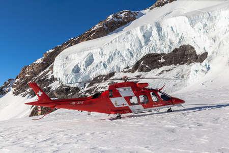 Jungfraujoch, Switzerland - December 28, 2015 - Rescue helicopter of Rega stopped on the glacier of Jungfraujoch, Switzerland. Publikacyjne