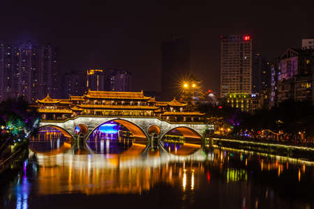 Night view of Anshun Bridge with beautiful illumination and reflection in Chengdu, Sichuan Province, China. The bridge crosses the Jin River. It contains a restaurant and is a popular eating location.