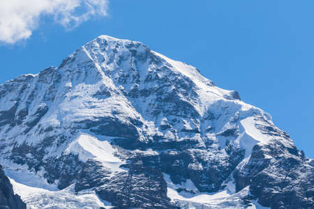 Close view of the famous peak Monch of the swiss Alps on Bernese Oberland in Switzerland. It is one of the main summits of the Bernese Alps, located between southern canton Bern and northern canton Valais.