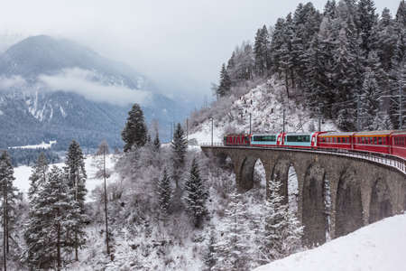 Famous sightseeing train running over viaduct in Switzerland, the Glacier Express in winter Imagens