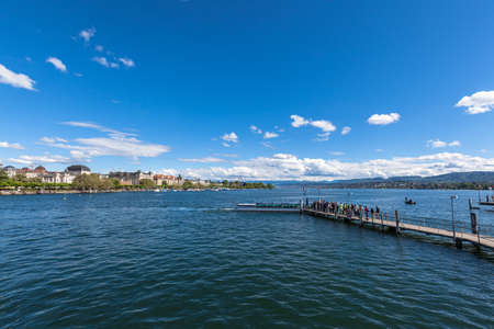 Panorama view of the Zurichsee (Zurich lake) and the cityscape of old town with Swiss Alps mountain range and blue sky cloud in background on a sunny summer day, Zurich, Switzerland