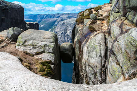 Close view of the famous boulder Kjeragbolten above the Lysefjorden on the mountain Kjerag in Forsand municipality in Rogaland county, Norway. Archivio Fotografico