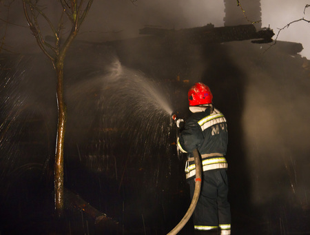 Firefighters extinguish the house. Night, its snowing.