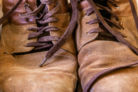 Old, leather shoes. Shabby, brown skin Tattered shoelaces Close-up