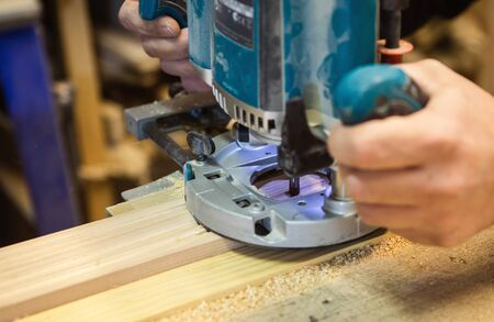 Work milling woodworking machine. Joiner mills a wooden detail.