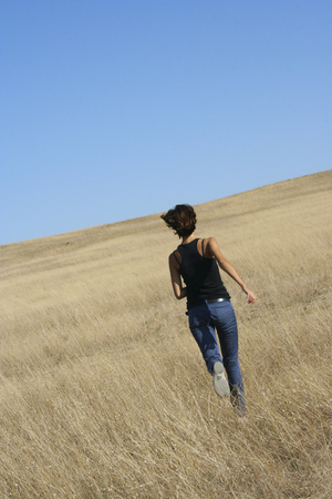 Adult girl running away through field. Beautiful warm day