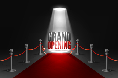 Grand opening event banner in spotlights. Red carpet between two barriers. Red ribbon cut ceremony.