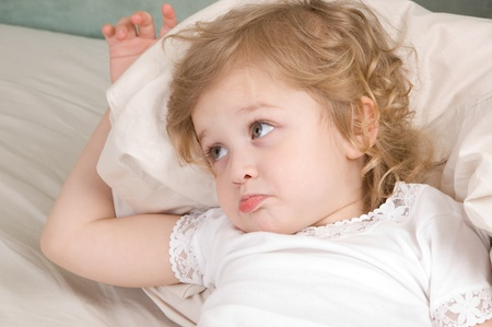 Sad adorable little girl in the bed closeup Stock Photo - 10060377