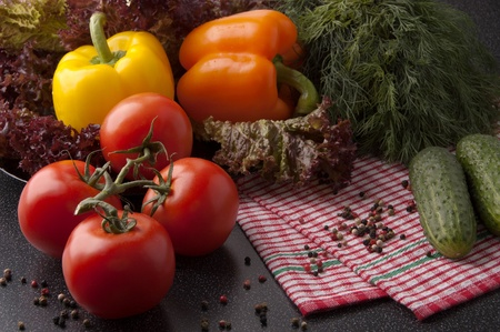 Three red tomatoes,cucumbers ,orange and  yellow peppers and lettuce on  plaid napkin