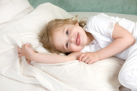 Adorable little girl rest in bed tongue hanging out