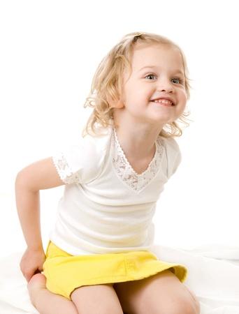 スマイリー白い背景の上に座っている黄色のスカートを着て幸せな女の子