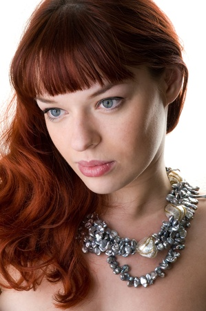 sad red haired girl and a pearl necklace close-up