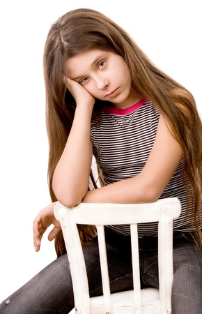 Pretty girl in the age of eleven sitting on a chair isolated on white photo
