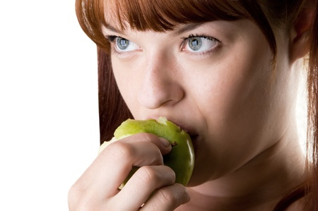 red haired girl eating green appl closeup