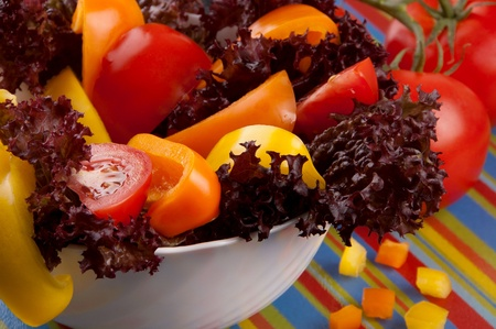 Bbowl of salad  made of red tomatoes,orange and  yellow peppers and lettuce and  tomatoes on striped board for slicing Stock Photo