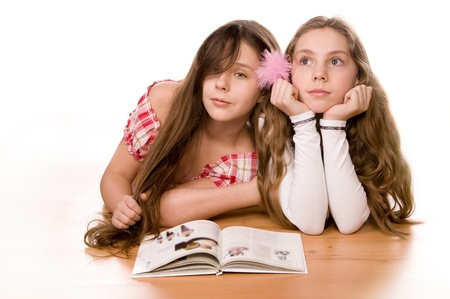 Two girls in the age of ten and eleven reading book on the floor on white  photo