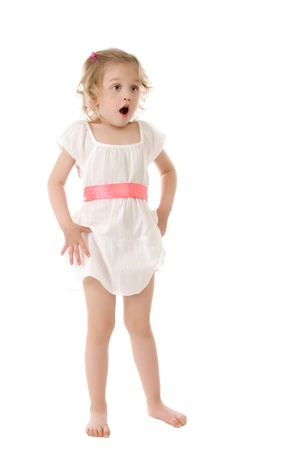 amazed little girl wearing a white dress standing on white background