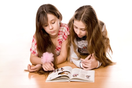 Two girls in the age of ten and eleven reading book on the floor on white