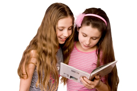Two girls in the age of ten and eleven reading book isolated on white Stock Photo