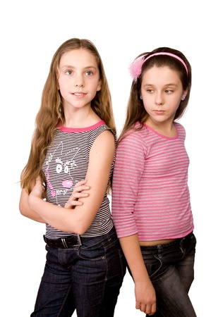 Two girls in the age of ten and eleven standing  isolated on white background