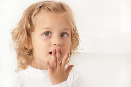 Scared amazed little girl dressed in white standing on white background