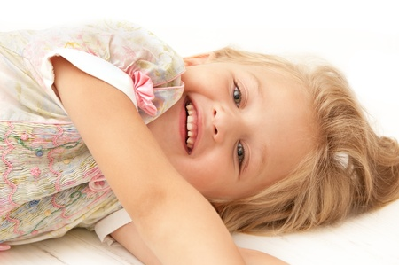 smiling little girl resting on the floor close-up Stock Photo