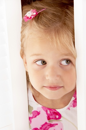 Little blonde girl look out of the door close-up photo