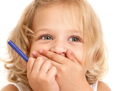 笑っている小さな女の子は彼女の手と彼女の手のクローズ アップ ホワイト バック グラウンド上に鉛筆を保持している彼女の口をカバーします。