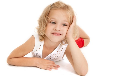 Little girl lying on the floor, looking down and dreaming on  white background